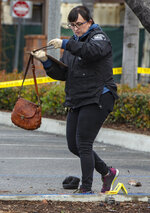 Heather Barclay, an accident investigator with the Fullerton Police Department, recovers a purse that was lodged underneath a pickup truck in the aftermath of a car accident, Sunday, Feb. 10, 2019, in Fullerton, Calif. Authorities say a suspected drunken driver was arrested after his pickup truck plowed into a crowd on a sidewalk, injuring multiple people, including some victims who were trapped under the vehicle. (Mindy Schauer/The Orange County Register via AP)