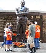 Fans gather at a statue of Denver Broncos owner Pat Bowlen outside Mile High Stadium, the home of the franchise, Friday, June 14, 2019, in Denver. Bowlen died Thursday night. (AP Photo/David Zalubowski)