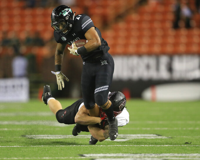 Hawaii running back Fred Holly III (21) gets pulled down by UNLV linebacker Bailey Laolagi (48) uring the fourth quarter of an NCAA college football game, Saturday, Nov. 17, 2018, in Honolulu. Hawaii defeated UNLV 35-28. (AP Photo/Marco Garcia)