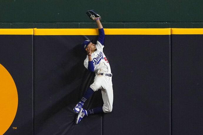 Los Angeles Dodgers right fielder Mookie Betts robs Atlanta Braves' Freddie Freeman of a home run during the fifth inning in Game 7 of a baseball National League Championship Series Sunday, Oct. 18, 2020, in Arlington, Texas. (AP Photo/Tony Gutierrez)
