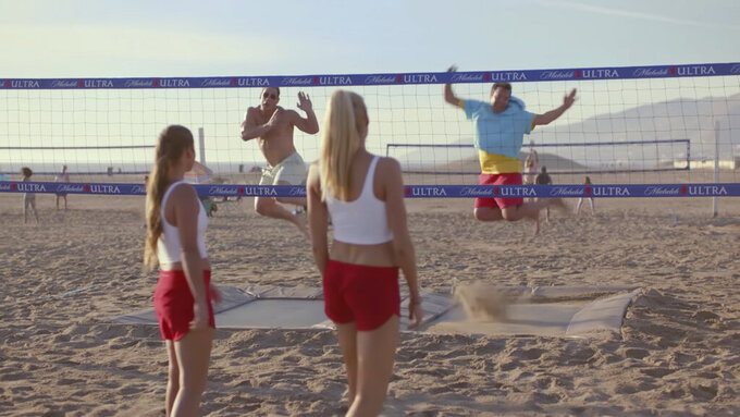 """This undated image provided by Michelob ULTRA shows from left, Brooke Sweat, John Cena, Kerri Walsh Jennings and Jimmy Fallon in a scene from the company's 2020 Super Bowl NFL football spot. Wrestler-turned-actor John Cena tries to convince Tonight Show host Jimmy Fallon that there's a """"lighter side"""" to working out, with cameos by Tonight show band The Roots and runner Usain Bolt. (Michelob ULTRA via AP)"""