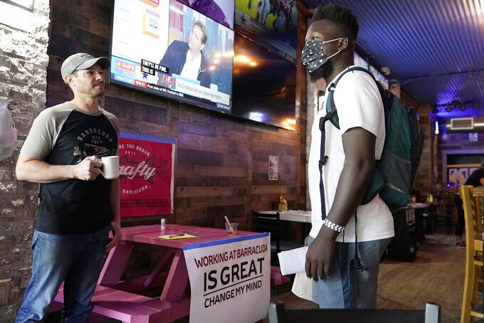 """Sudy Gervais, right, talks with Lee Kessler, the owner of the Barracuda Taphouse & Grill, left, about a potential job at a job fair featuring local businesses in the Coconut Grove neighborhood of Miami, Wednesday, Sept. 8, 2021. U.S. economic activity """"downshifted"""" in July and August due to rising concerns about COVID's delta variant, as well as supply chain problems and labor shortages, the Federal Reserve's latest survey of the nation's business conditions revealed.  (AP Photo/Lynne Sladky)"""