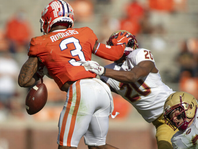 Clemson wide receiver Amari Rodgers (3) fumbles the ball as he stiff-arms Boston College defensive back Elijah Jones (20) during the second half of an NCAA college football game  Saturday, Oct. 31, 2020, in Clemson, S.C. (Josh Morgan/Pool Photo via AP)
