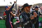 Mercedes driver Lewis Hamilton of Britain gestures as Red Bull driver Max Verstappen of the Netherlands celebrates in background after clinching the pole position following the qualifying session for Sunday's Formula One Dutch Grand Prix at the Zandvoort racetrack, Netherlands, Saturday, Sept. 4, 2021. Hamilton set the second fastest time. (AP Photo/Francisco Seco, Pool)