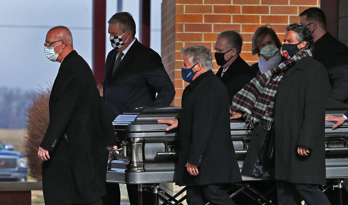 Pall bearers, including Mario Andretti, center, walk the casket out after the Celebration of Life service for Mario's twin brother, Aldo Andretti, at St. Malachy Catholic Church in Brownsburg, Ind., Wednesday, Jan. 13, 2021. Mario feels the same pain as so many others these days. His wife died two years ago, long before the pandemic. And his beloved nephew lost a brutal battle with colon cancer. But then COVID-19 claimed his twin brother Aldo and one of the greatest racers of all time is not immune from the loneliness and depression sweeping the world. (Kelly Wilkinson/The Indianapolis Star via AP)