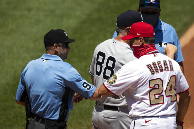 Home plate umpire Will Little (93) greets Washington Nationals bench coach Tim Bogar (24) with an elbow-bump before a baseball game against the New York Yankees at Nationals Park, Sunday, July 26, 2020, in Washington. (AP Photo/Alex Brandon)