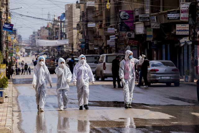Medical workers oversee the disinfection of the streets to prevent the spread of coronavirus in Qamishli, Syria, Tuesday, March 24, 2020. (AP Photo/Baderkhan Ahmad)
