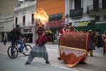 """A member of the Brazilian theater group Clowns of Shakespeare spits fire during a performance in Bogota, Colombia, Saturday, Oct. 26, 2019. The troupe's play titled """"Abrazo,"""" or Hug, is among the growing list of shows, plays, conferences and other artistic projects that have been abruptly canceled in Brazil since the nation's President Jair Bolsonaro took office Jan. 1, after the troupe talked politics with the audience during the show's debut. (AP Photo/Ivan Valencia)"""