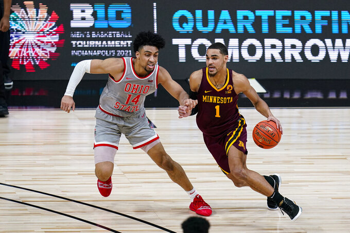 Minnesota guard Tre' Williams (1) drives on Ohio State forward Justice Sueing (14) in the first half of an NCAA college basketball game at the Big Ten Conference tournament in Indianapolis, Thursday, March 11, 2021. (AP Photo/Michael Conroy)