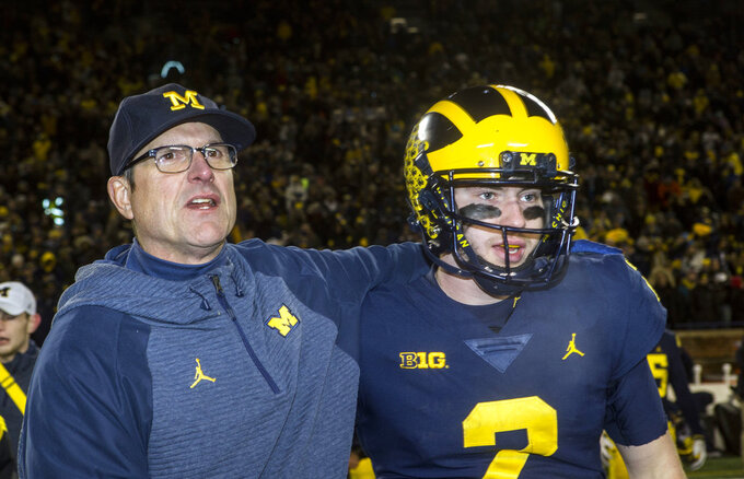 Michigan head coach Jim Harbaugh, left, puts an arm around Michigan quarterback Shea Patterson, right, after an NCAA college football game against Indiana in Ann Arbor, Mich., Saturday, Nov. 17, 2018. Michigan won 31-20. (AP Photo/Tony Ding)