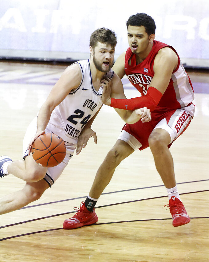 Utah State guard Rollie Worster (24) drives as UNLV forward Devin Tillis (30) defends during the first half of an NCAA college basketball game in the quarterfinals of the Mountain West Conference men's tournament Thursday, March 11, 2021, in Las Vegas. (AP Photo/Isaac Brekken)
