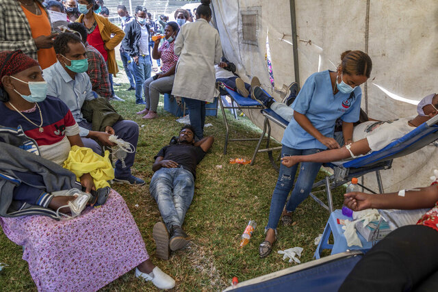 A man lies down after giving blood at a blood drive in support of the country's military, at a stadium in the capital Addis Ababa, Ethiopia Thursday, Nov. 12, 2020. Rallies occurred in multiple cities in support of the federal government's military offensive against the Tigray regional government, the Tigray People's Liberation Front. (AP Photo/Mulugeta Ayene)