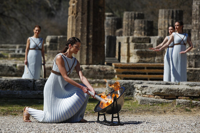 Greek actress Xanthi Georgiou, playing the role of the High Priestess, lights up the torch during the flame lighting ceremony at the closed Ancient Olympia site, birthplace of the ancient Olympics in southern Greece, Thursday, March 12, 2020. Greek Olympic officials are holding a pared-down flame-lighting ceremony for the Tokyo Games due to concerns over the spread of the coronavirus. Both Wednesday's dress rehearsal and Thursday's lighting ceremony are closed to the public, while organizers have slashed the number of officials from the International Olympic Committee and the Tokyo Organizing Committee, as well as journalists at the flame-lighting. (AP Photo/Thanassis Stavrakis)