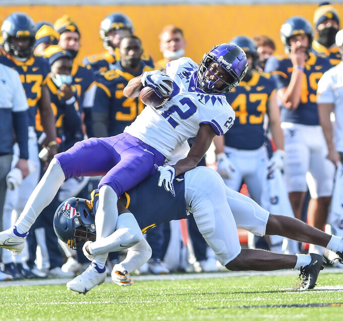 TCU wide receiver Blair Conwright (22) makes a catch and is tackled by West Virginia safety Jake Long (22) during the second half of an NCAA college football game on Saturday, Nov. 14, 2020, in Morgantown, W.Va. (William Wotring/The Dominion-Post via AP)