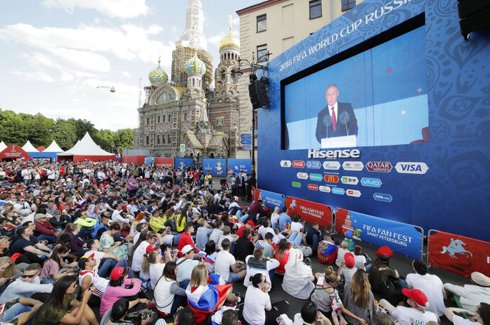 People watch a speech of Russian President Vladimir Putin on a huge screen prior the 2018 soccer World Cup match between Russia and Saudi Arabia at a fan zone in St.Petersburg, Russia, Thursday, June 14, 2018. (AP Photo/Dmitri Lovetsky)