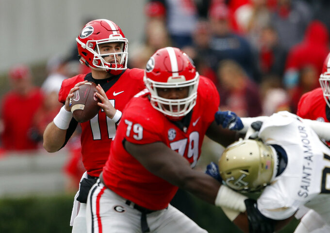 Georgia quarterback Jake Fromm (11) throws from behind the blocking of offensive lineman Isaiah Wilson (79) during the first half of an NCAA college football game against Georgia Tech, Saturday, Nov. 24, 2018, in Athens, Ga. (AP Photo/John Bazemore)