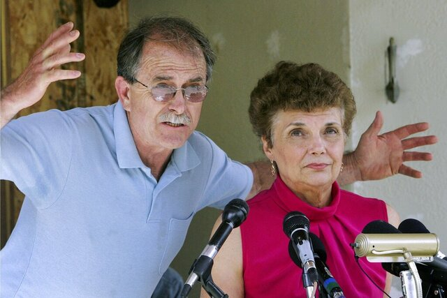 FILE - In this June 18, 2007, file photo, Ed and Elaine Brown talk to reporters during a news conference at their home in Plainfield, N.H. Years after they were imprisoned for amassing an arsenal of weapons at their fortress-like home, and holding U.S. marshals at bay after a tax evasion conviction, Elaine Brown said she is ashamed of her actions and seeks a divorce while awaiting re-sentencing in 2020 in light of a recent U.S. Supreme Court ruling. (AP Photo/Jim Cole, File)