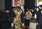 In this photo released by Indonesian Presidential Palace, Indonesian President Joko Widodo, wearing a face mask as a precaution against the new coronavirus outbreak, arrives to deliver his national address before the parliament members in Jakarta, Indonesia, Friday, Aug. 14, 2020. Indonesia's president called on all citizens to turn the COVID-19 crisis into an advancement opportunity and pledged health care reforms in an address Friday ahead of the country's 75th anniversary of independence. (Agus Suparto/Presidential Palace via AP)