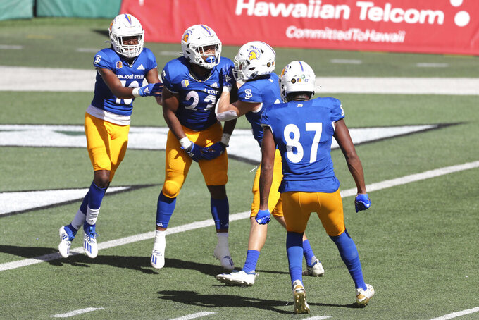 Teammates celebrate with San Jose State running back Tyler Nevens (23) after he made a touchdown against Hawaii in the first half of an NCAA college football game Saturday, Dec. 5, 2020, in Honolulu. (AP Photo/Marco Garcia)