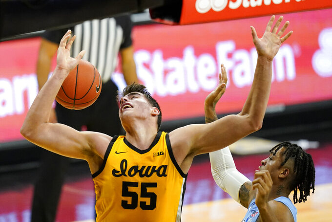 Iowa center Luka Garza (55) fight for a rebound with North Carolina forward Armando Bacot, right, during the first half of an NCAA college basketball game, Tuesday, Dec. 8, 2020, in Iowa City, Iowa. (AP Photo/Charlie Neibergall)