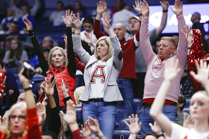 Arkansas fans cheer in the second half of an NCAA college basketball game between Arkansas and Vanderbilt in the Southeastern Conference Tournament Wednesday, March 11, 2020, in Nashville, Tenn. Arkansas won 86-73. The Southeastern Conference has joined the rest of the Power Five leagues in closing off its men's basketball tournament to fans after Wednesday. The SEC opened its tourney after the NCAA announced that only family and essential personnel would attend its men's and women's tournament games that begin around the country next week. (AP Photo/Mark Humphrey)